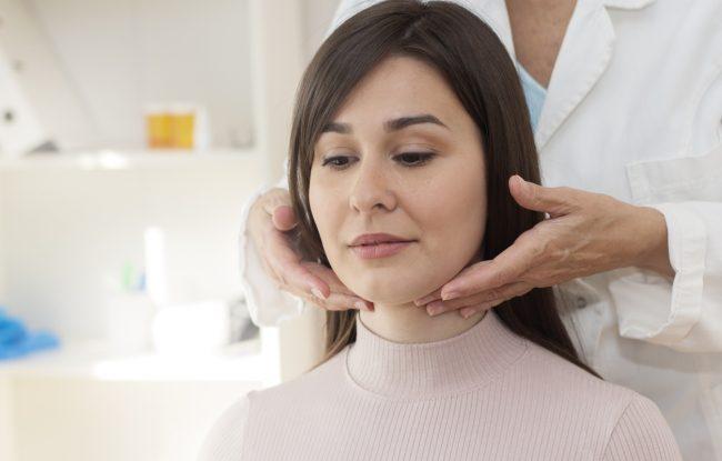 Demonstration of doctor examining patient neck